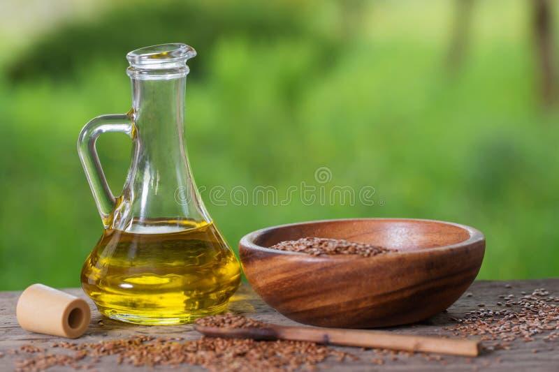 Lnów ziarna i linseed olej w szklanym dzbanku na drewnianym stole obrazy royalty free