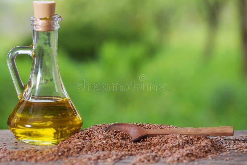 Lnów ziarna i linseed olej w szklanym dzbanku na drewnianym stole zdjęcia stock
