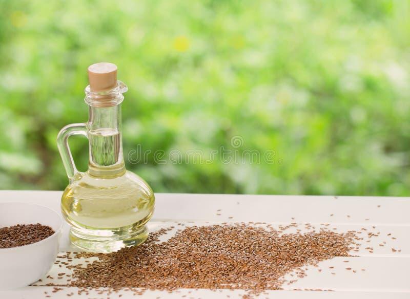 Lnów ziarna i linseed olej w szklanym dzbanku na drewnianym stole fotografia royalty free