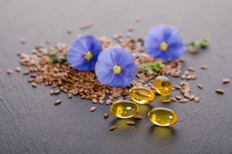 Lnów ziarna, piękno kwiat i olej w nakrętkach na popielatym tle, zdjęcia stock