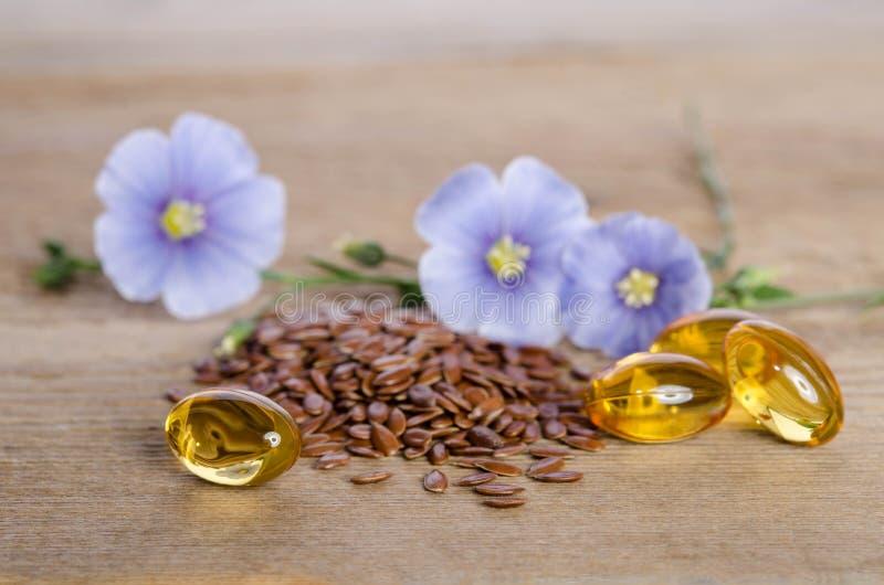 Lnów ziarna, piękno kwiaty i olej w nakrętkach na drewnianym tle, fotografia stock