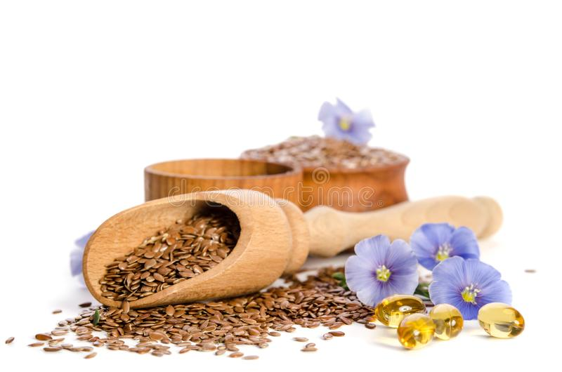 Lnów ziarna w drewnianej miarce, pucharze z olejem i oleju w nakrętkach, fotografia stock