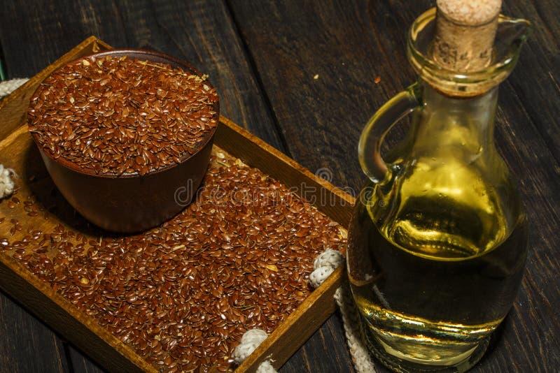 Lnów ziarna w glinianym pucharu i linseed oleju w szklanym słoju na drewnianym stole Flaxseed olej jest bogaty w omega-3 kwasie zdjęcia stock