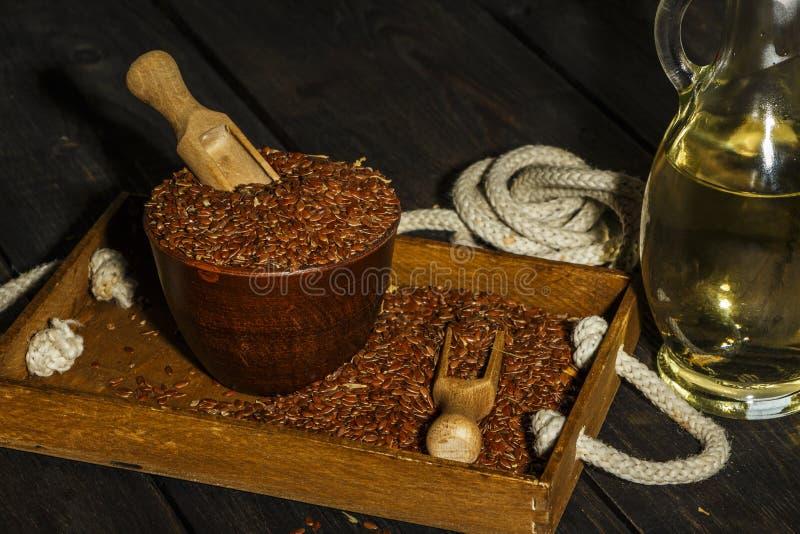 Lnów ziarna w glinianym pucharu i linseed oleju w szklanym słoju na drewnianym stole Flaxseed olej jest bogaty w omega-3 kwasie obraz stock
