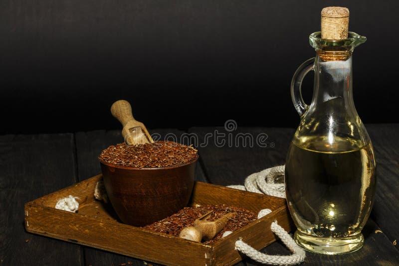 Lnów ziarna w glinianym pucharu i linseed oleju w szklanym słoju na drewnianym stole Flaxseed olej jest bogaty w omega-3 kwasie zdjęcia royalty free