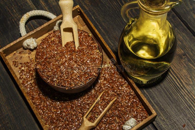 Lnów ziarna w glinianym pucharu i linseed oleju w szklanym słoju na drewnianym stole Flaxseed olej jest bogaty w omega-3 kwasie zdjęcie stock
