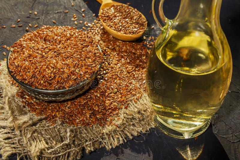 Lnów ziarna w glinianym pucharu i linseed oleju w szklanym słoju na drewnianym stole Flaxseed olej jest bogaty w omega-3 kwasie obraz royalty free
