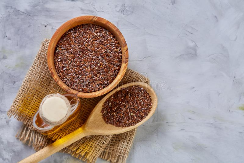 Lnów ziarna w pucharu i flaxseed oleju w szklanej butelce na świetle textured tło, odgórny widok, zakończenie, selekcyjna ostrość zdjęcie royalty free