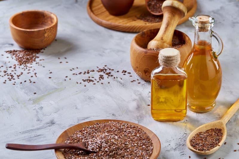 Lnów ziarna w pucharu i flaxseed oleju w szklanej butelce na świetle textured tło, odgórny widok, zakończenie, selekcyjna ostrość obraz royalty free