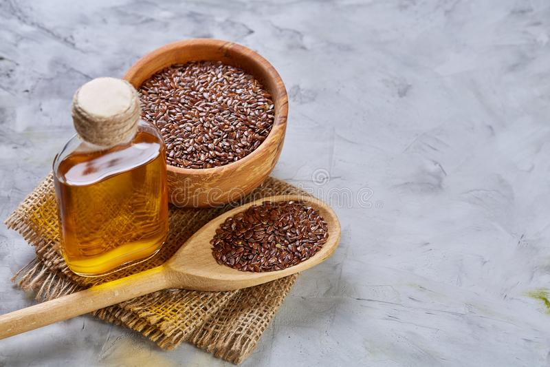 Lnów ziarna w pucharu i flaxseed oleju w szklanej butelce na świetle textured tło, odgórny widok, zakończenie, selekcyjna ostrość obrazy stock