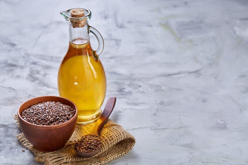 Lnów ziarna w pucharu i flaxseed oleju w szklanej butelce na świetle textured tło, odgórny widok, zakończenie, selekcyjna ostrość obrazy royalty free
