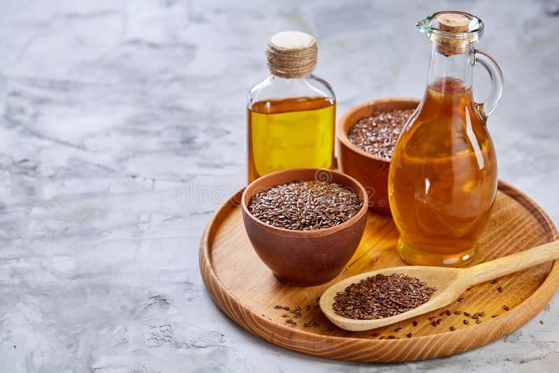Lnów ziarna w pucharu i flaxseed oleju w szklanej butelce na świetle textured tło, odgórny widok, zakończenie, selekcyjna ostrość zdjęcie stock