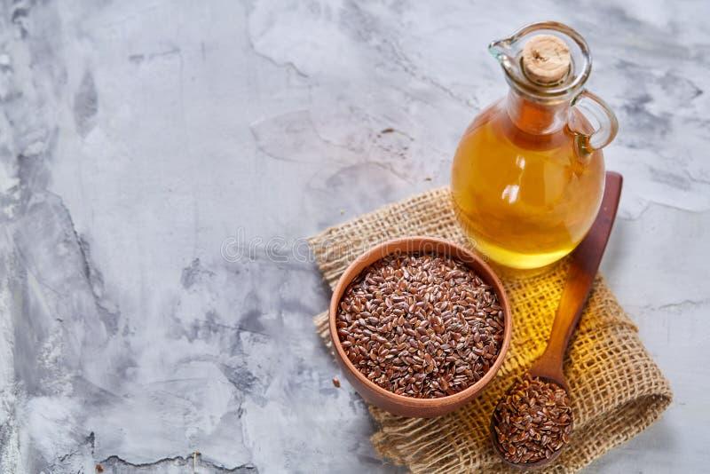 Lnów ziarna w pucharu i flaxseed oleju w szklanej butelce na świetle textured tło, odgórny widok, zakończenie, selekcyjna ostrość zdjęcia stock