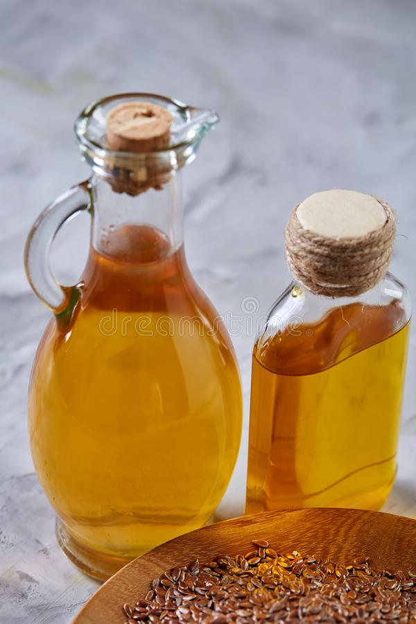 Lnów ziarna w pucharu i flaxseed oleju w szklanej butelce na świetle textured tło, odgórny widok, zakończenie, selekcyjna ostrość fotografia stock