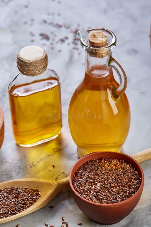 Lnów ziarna w pucharu i flaxseed oleju w szklanej butelce na świetle textured tło, odgórny widok, zakończenie, selekcyjna ostrość fotografia royalty free