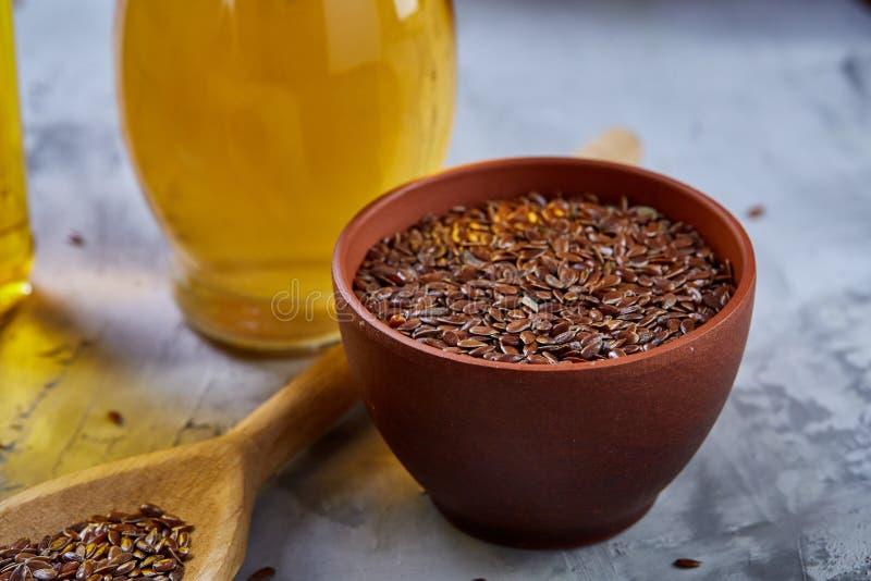 Lnów ziarna w pucharu i flaxseed oleju w szklanej butelce na świetle textured tło, odgórny widok, zakończenie, selekcyjna ostrość zdjęcia royalty free