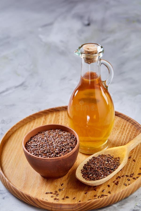 Lnów ziarna w pucharu i flaxseed oleju w szklanej butelce na białym tle, odgórny widok, zakończenie, selekcyjna ostrość obraz royalty free