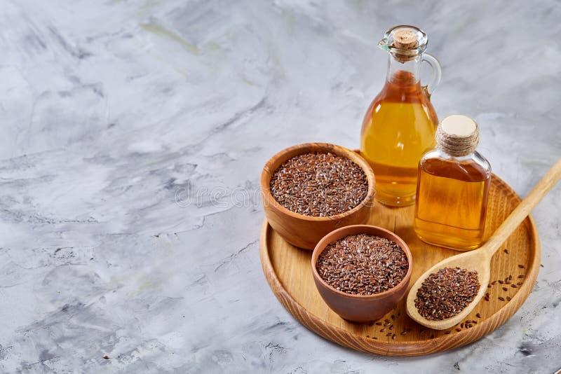 Lnów ziarna w pucharu i flaxseed oleju w szklanej butelce na białym tle, odgórny widok, zakończenie, selekcyjna ostrość zdjęcia stock