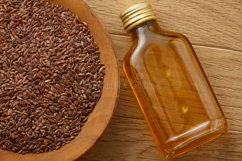 Lnów ziarna w pucharu i flaxseed oleju w szklanej butelce na drewnianym tle, odgórny widok, zakończenie, selekcyjna ostrość obraz stock