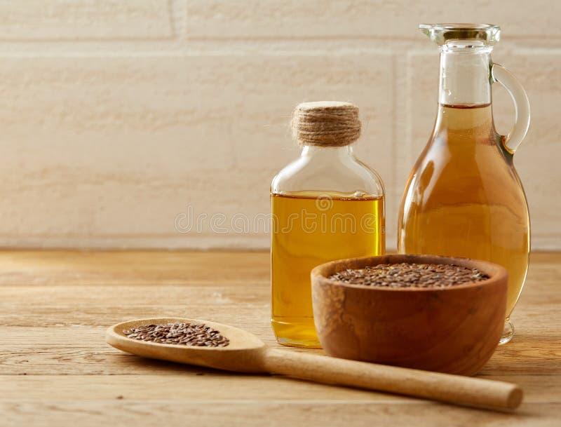 Lnów ziarna w pucharu i flaxseed oleju w szklanej butelce na drewnianym tle, odgórny widok, zakończenie, selekcyjna ostrość fotografia royalty free