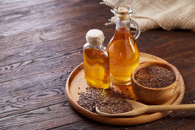 Lnów ziarna w pucharu i flaxseed oleju w szklanej butelce na drewnianym tle, odgórny widok, zakończenie, selekcyjna ostrość obrazy stock