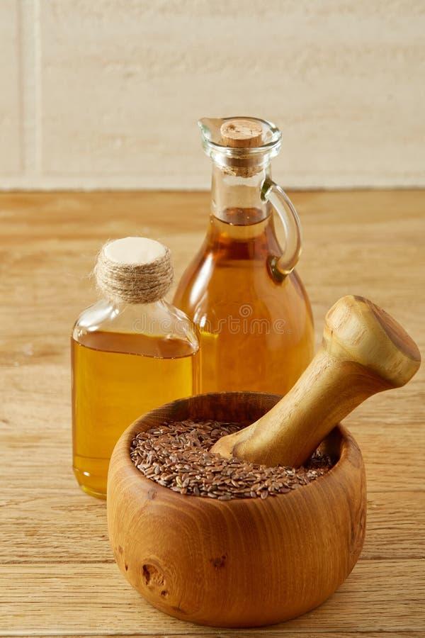 Lnów ziarna w pucharu i flaxseed oleju w szklanej butelce na drewnianym tle, odgórny widok, zakończenie, selekcyjna ostrość obraz royalty free