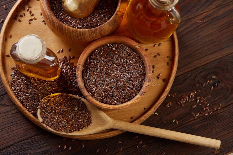 Lnów ziarna w pucharu i flaxseed oleju w szklanej butelce na drewnianym tle, odgórny widok, zakończenie, selekcyjna ostrość zdjęcie royalty free