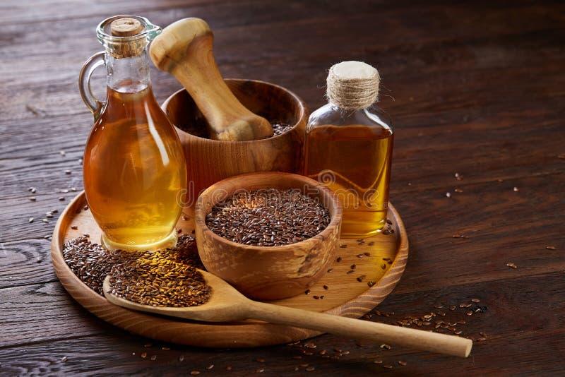 Lnów ziarna w pucharu i flaxseed oleju w szklanej butelce na drewnianym tle, odgórny widok, zakończenie, selekcyjna ostrość zdjęcia royalty free