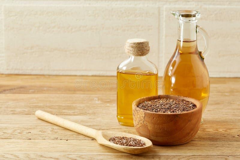 Lnów ziarna w pucharu i flaxseed oleju w szklanej butelce na drewnianym tle, odgórny widok, zakończenie, selekcyjna ostrość fotografia stock
