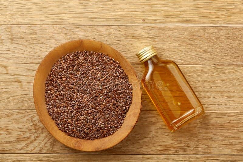 Lnów ziarna w pucharu i flaxseed oleju w szklanej butelce na drewnianym tle, odgórny widok, zakończenie, selekcyjna ostrość zdjęcia stock