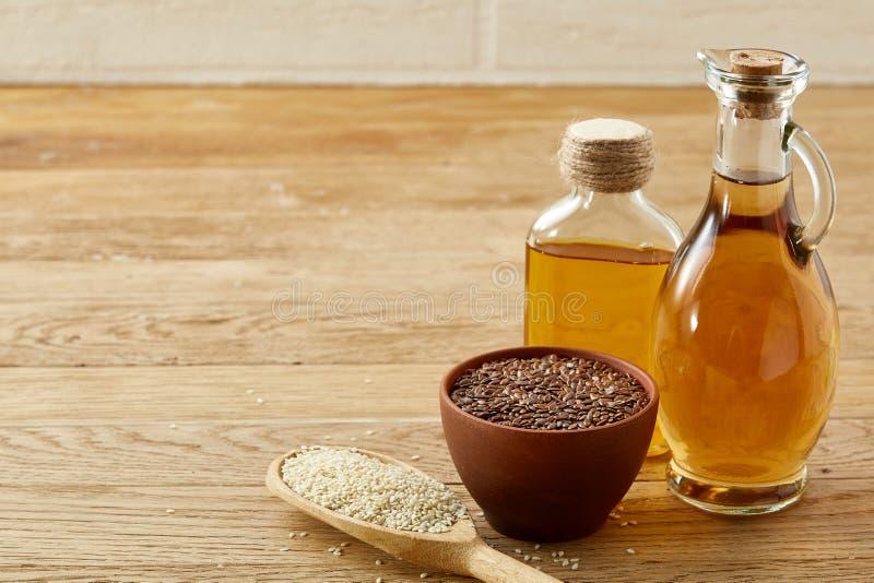 Lnów ziarna w pucharze, flaxseed olej w szklanej butelce, łyżka z wzrostem na drewnianym tle, zakończenie, selekcyjna ostrość obrazy royalty free