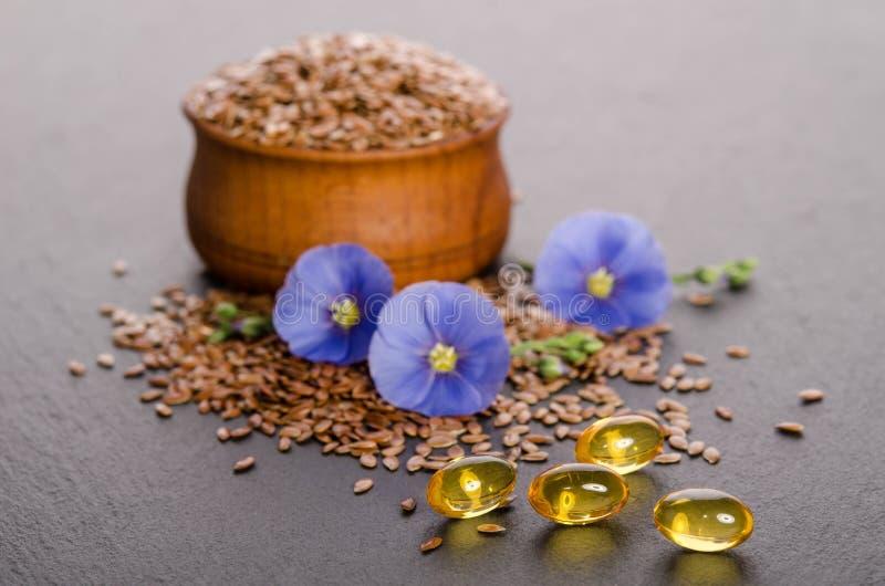 Lnów ziarna w pucharze, piękno kwiacie i oleju w nakrętkach drewnianych, fotografia royalty free