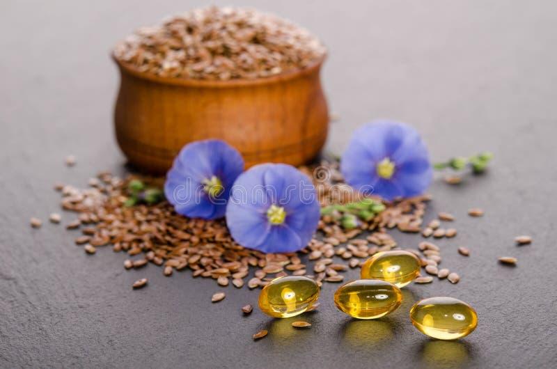 Lnów ziarna w pucharze, piękno kwiatach i oleju w nakrętkach na popielatym tle drewnianych, zdjęcia royalty free