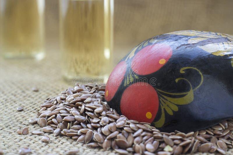 Lnów ziarna w stosie z łyżki i linseed złotym olejem w glas fotografia stock