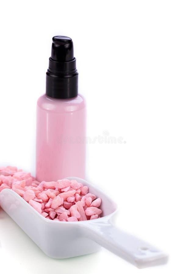 Loção cor-de-rosa do corpo no distribuidor e no sal do aroma isolados imagens de stock