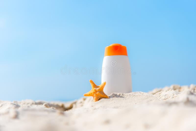 Loção protetora da proteção solar ou do sunblock e do sunbath nas garrafas plásticas brancas na praia tropical, acessórios do ver imagens de stock royalty free