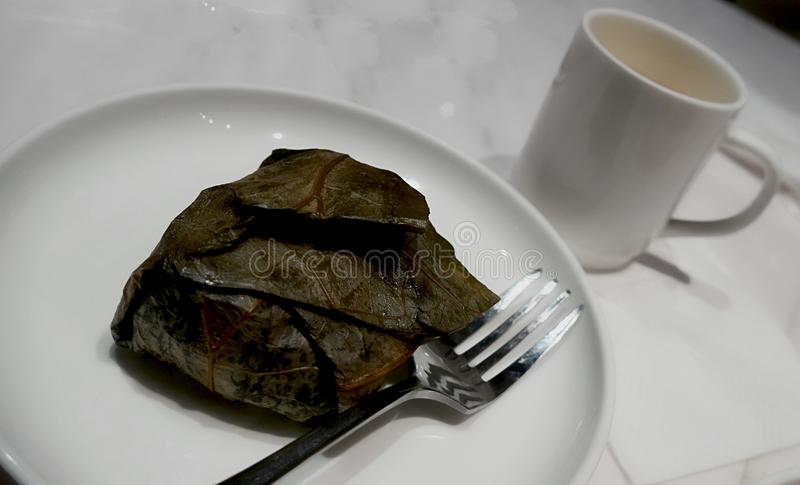 Lo mai gai- zawijający i słuzyć w talerzu, z rozwidleniem i filiżanką fotografia stock