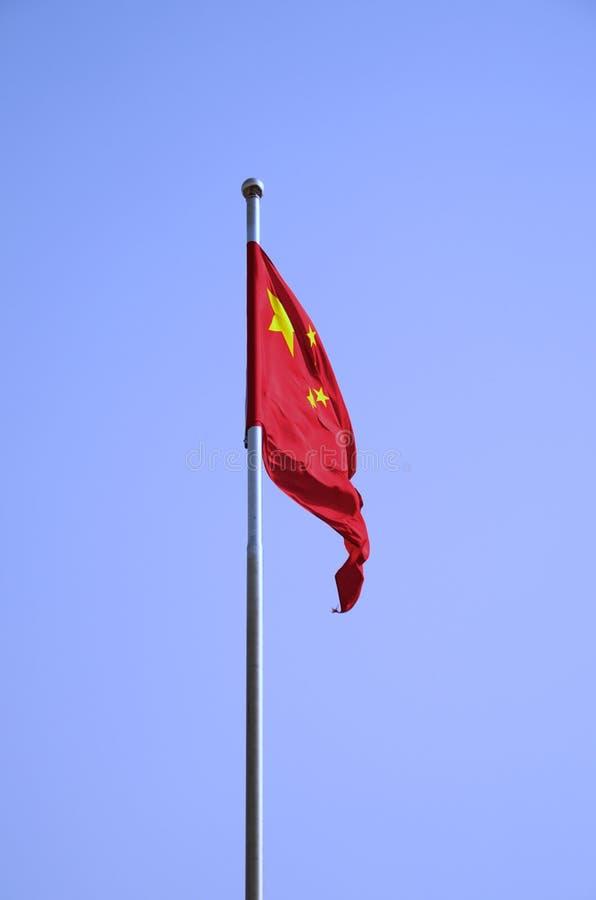 Lo sbattimento cinese della bandiera contro un cielo blu solido immagini stock