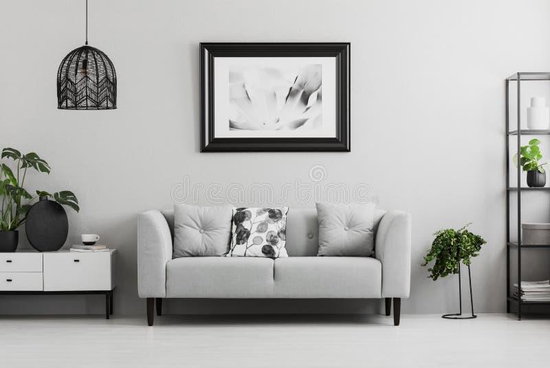 Lo scaffale industriale nero e una pianta stanno accanto ad un sofà ricoperto in un interno grigio del salone con il posto per un fotografia stock libera da diritti