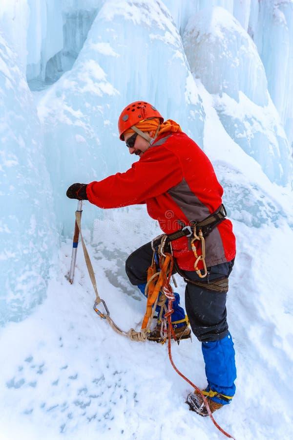 Lo scalatore con l'ascia di ghiaccio scala il ghiacciaio immagini stock libere da diritti