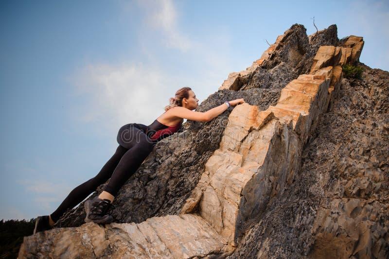 Lo scalatore estremo femminile conquista la roccia ripida immagini stock libere da diritti