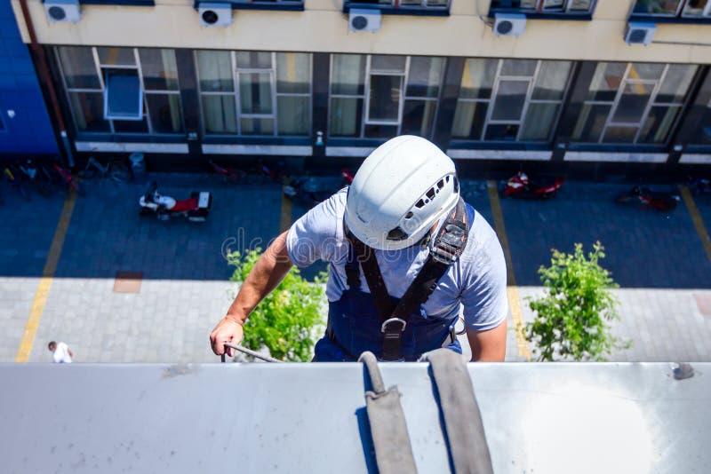 Lo scalatore industriale è lavare, pulente la facciata di un offic moderno fotografia stock
