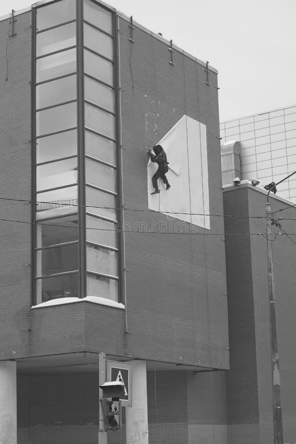 Lo scalatore industriale in bianco e nero rimuove un'insegna bianca da un muro di mattoni fotografia stock libera da diritti