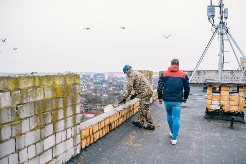 Lo scalatore industriale considera la possibilità della discesa da un tetto del grattacielo fotografia stock