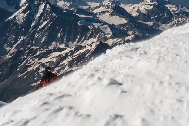 Lo scalatore scala la sommità innevata fotografia stock libera da diritti