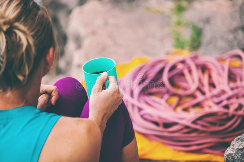 Lo scalatore sta bevendo da una tazza fotografia stock