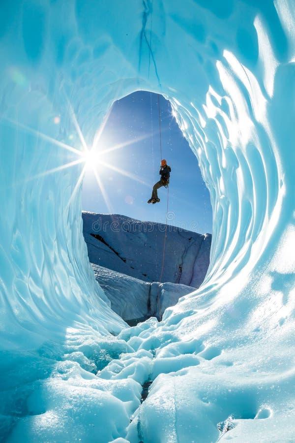Lo scalatore su ghiaccio rappels nella caverna di ghiaccio sul ghiacciaio di Matanuska nella regione selvaggia d'Alasca immagine stock