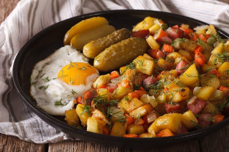 Lo scandinavo ha fritto le patate con le salsiccie, uova ed ha marinato i clos immagini stock