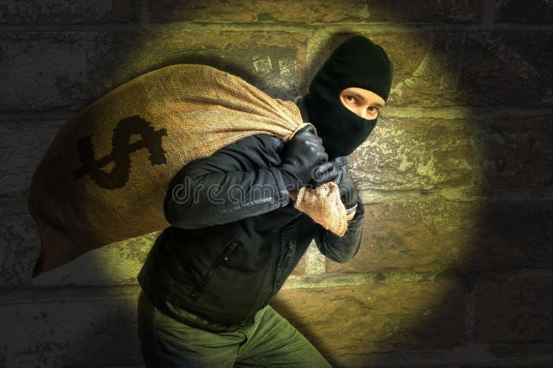 Lo scassinatore con la borsa piena di soldi catched con luce istantanea alla notte immagini stock libere da diritti