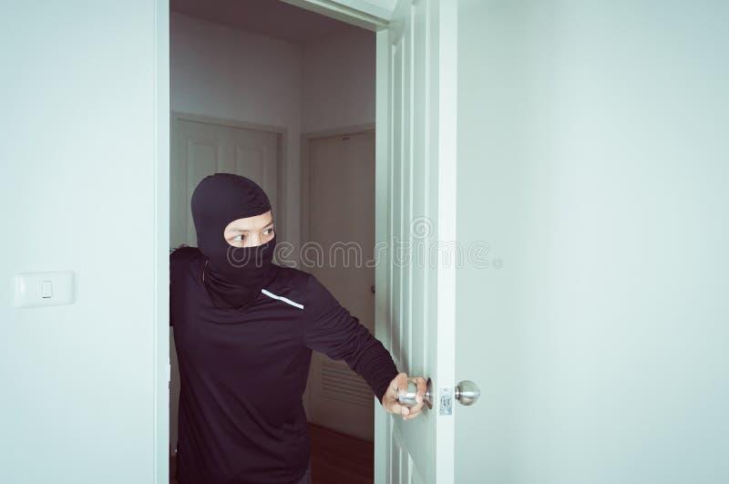 Lo scassinatore nella maschera nera che guarda ed apre la porta e rubare qualcosa dalla casa fotografia stock libera da diritti